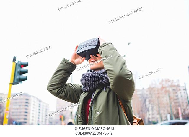 Young woman outdoors, wearing virtual reality headset