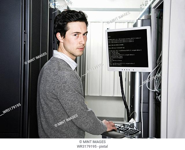 Caucasian male technician working on computer servers in a computer server farm