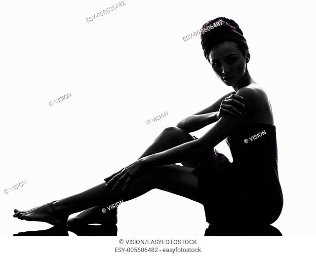 one beautiful asian young woman sitting on floor wrapped towel in silhouette studio isolated on white background