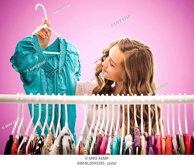 Caucasian teenager looking at shirt