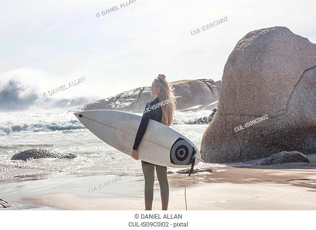 Young female surfer carrying surfboard looking out at ocean waves from beach, Cape Town, Western Cape, South Africa