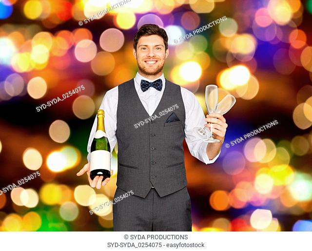 man with bottle of champagne and glasses at party