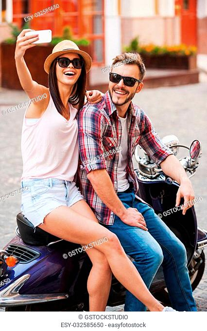 Selfie! Beautiful young loving couple sitting on scooter together and making selfie by their smart phone