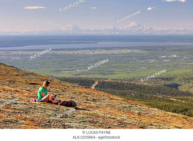 Woman looking at a tablet computer on Blueberry Hill with Denali (Mt. McKinley) in the distance, Chugach State Park, Anchorage, Southcentral Alaska, Spring, HDR