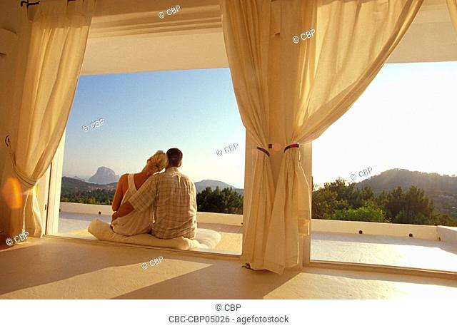 Young Couple Sitting At Open Window Watching The Sunset