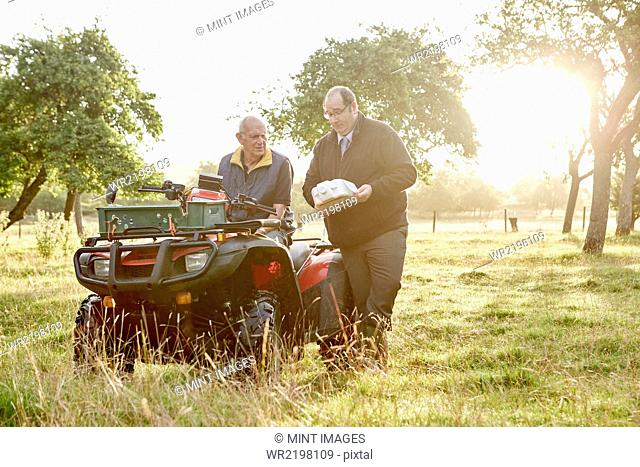 Two men, a farmer and a man with a clipboard, by a quadbike in an orchard