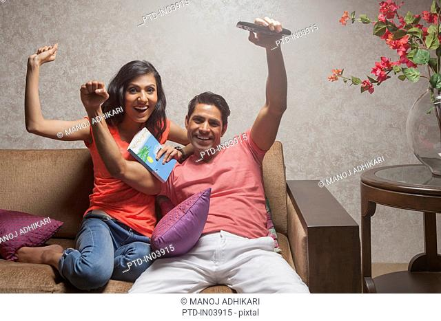 India, Man and woman watching television with arms raised