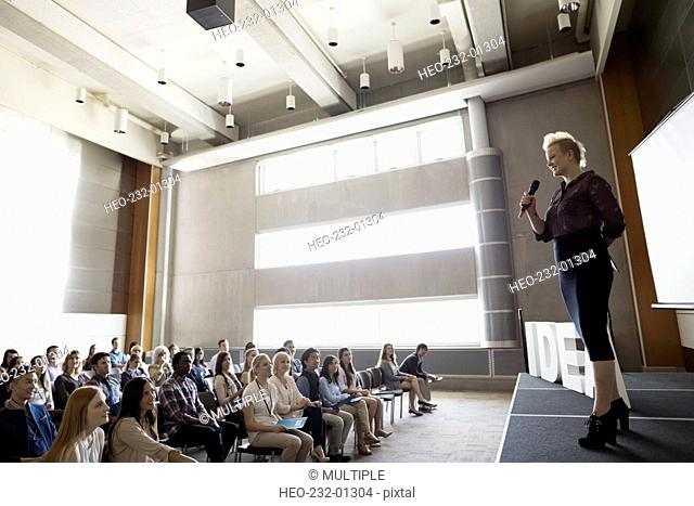 Speaker addressing audience stage next to Idea text