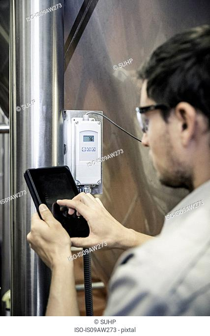 Over the shoulder view of young man in brewery using digital tablet