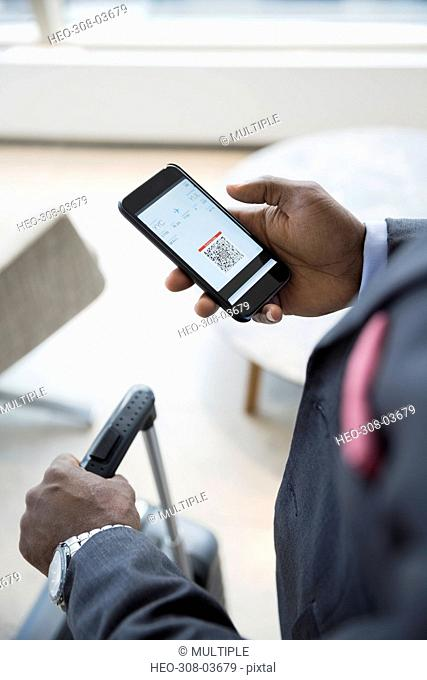 Businessman checking in on cell phone at airport