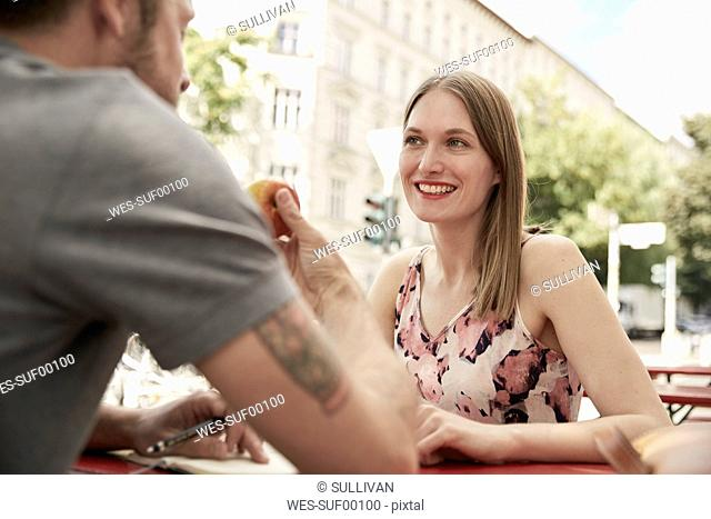 Smiling woman looking at man at a sidewalk cafe