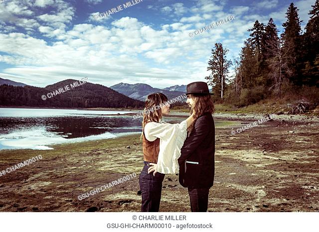 1970s Styled Couple facing each other in with Scenic Landscape in Background, Merrill Lake, Washington, USA