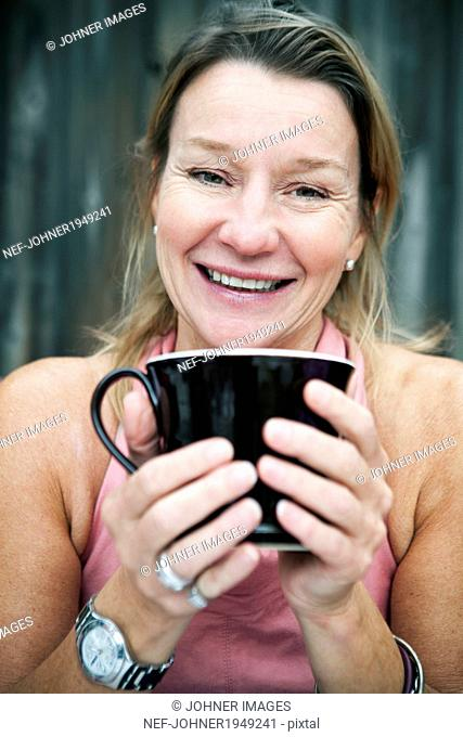 Smiling mature woman with mug, Sweden
