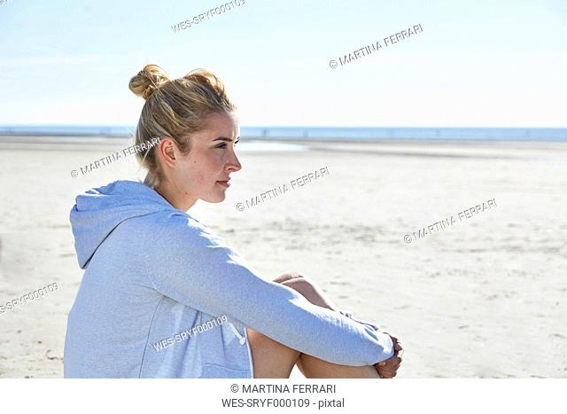 Young woman wearing hoodie sitting on the beach