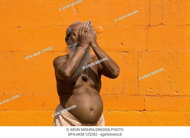 Hindu saint worshiping in Varanasi on orange background ; Uttar Pradesh ; India