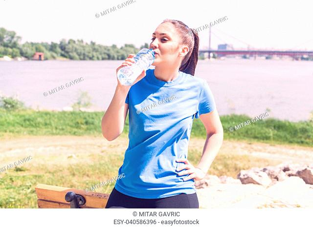 Fitness girl refresh, sporty woman drinking water after exercising outdoor
