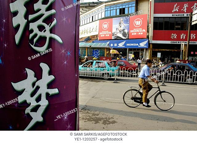 Man riding a bicycle along a busy city street in Datong, Shanxi,China