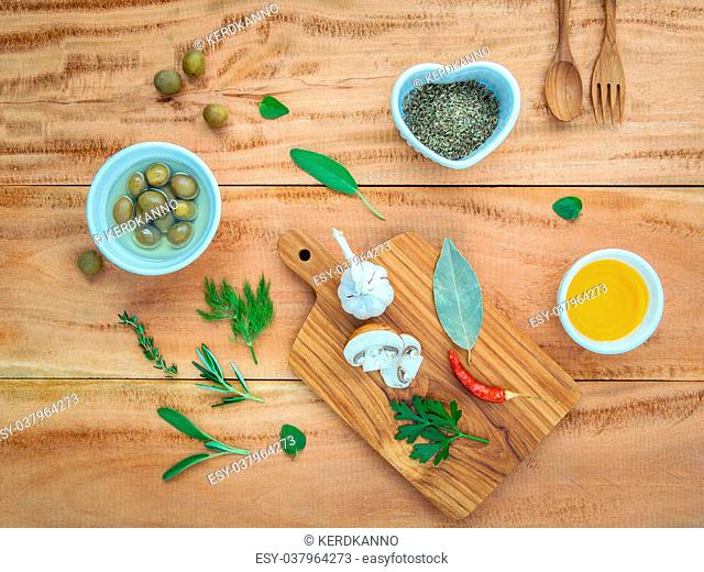 Different sorts of cooking oil,olive oil flavored and Sesame oil with spices herbs rosemary ,thyme,dill,sage mint and parsley and wooden spoon set up with...