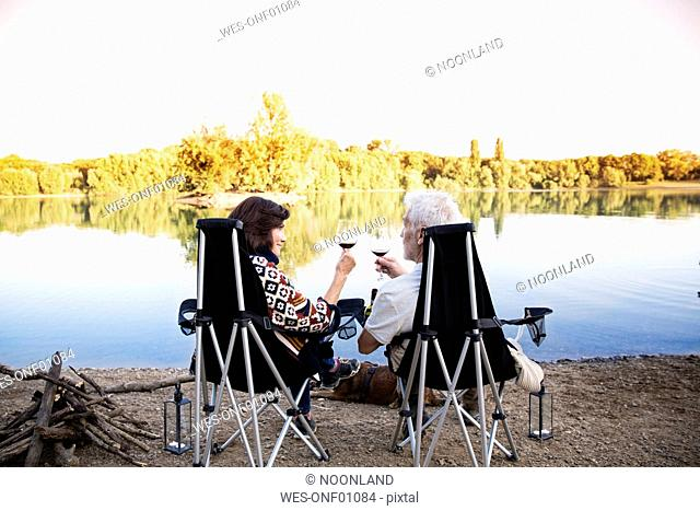 Senior couple clinking wine glasses at a lake in the evening