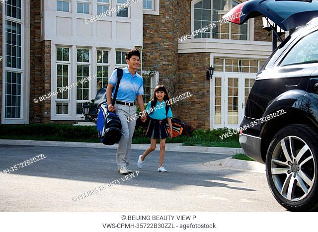 Oriental father taking daughter to car with golf bag