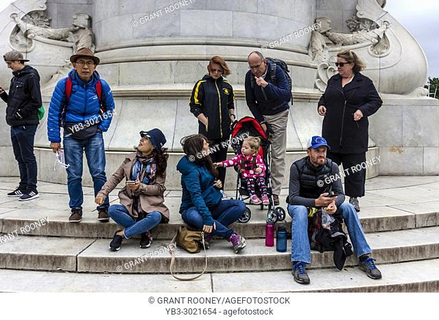 Tourists Sitting On The Steps Of The Victoria Memorial Outside Buckingham Palace, London, UK