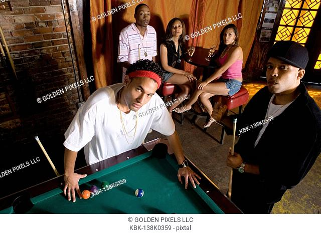 Portrait of young men in hip-hop fashion leaning against pool table