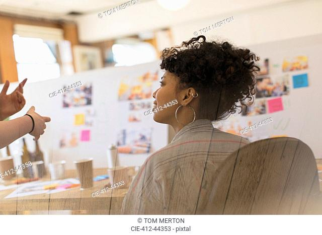 Creative female designer listening to colleague in office