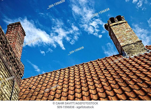 Traditional architectural roof tile detail and 2 chimneys detail in Brugge Sint Kruis, Brugge Bruges, Belgium