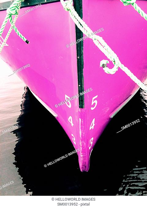 Ship's draft on pink hull of moored ship. The vertical distance between the waterline and the bottom of the hull