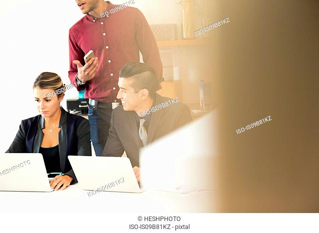 Businesswoman and men having meeting at office desk