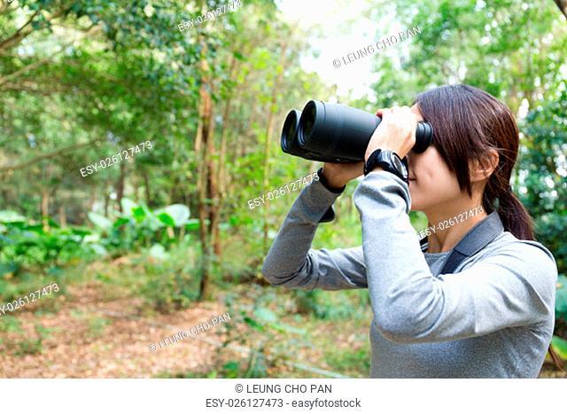 The side profile of Woman looking though binocular