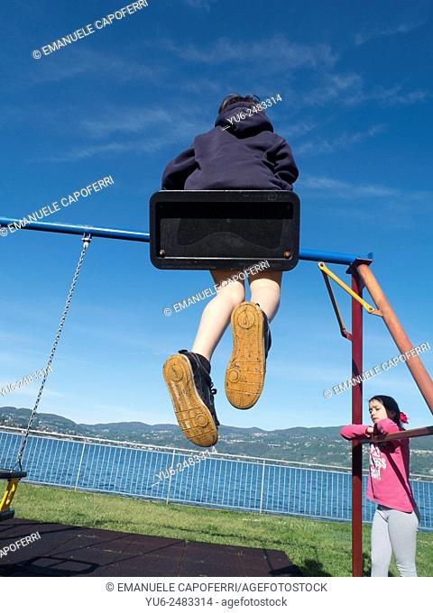 Children play at the playground with swings, Ispra, Varese, Lombardy, Italy