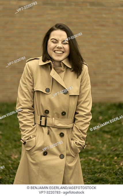 young happy laughing woman outdoors in city park during autumn season, wearing coat, candid emotion, closed eyes, pure happiness, in Munich, Bavaria, Germany