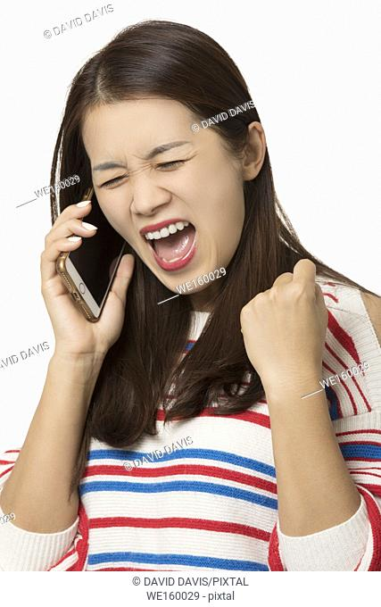 Angry Asian woman talking on a smartphone isolated on a white background