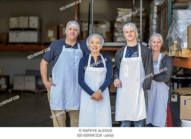Portrait of four factory workers smiling