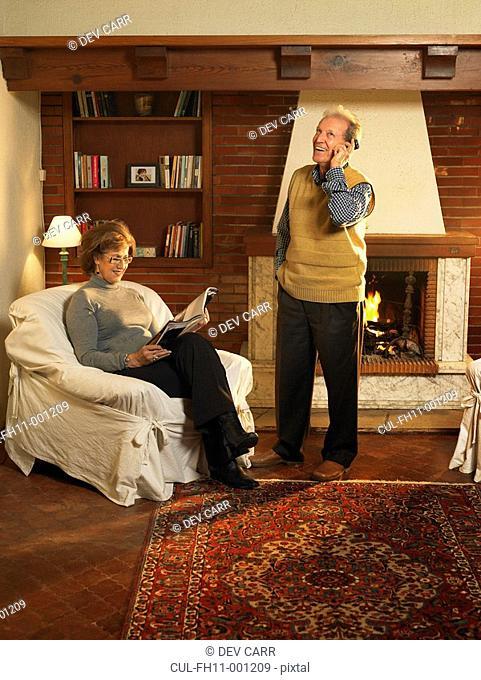 Senior man using mobile phone, woman reading, smiling