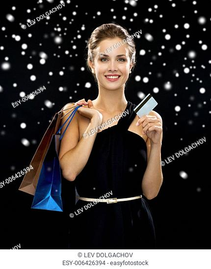 people, sale, money and holidays concept - smiling woman in dress with shopping bags and credit card over black snowy background