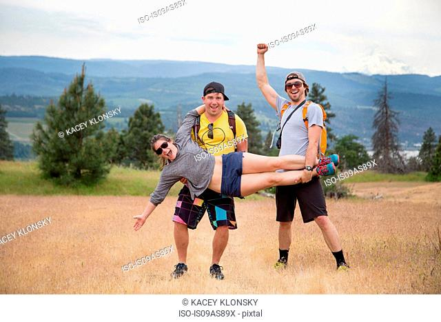 Small group of hikers, fooling around, two men holding woman up, laughing, celebrating