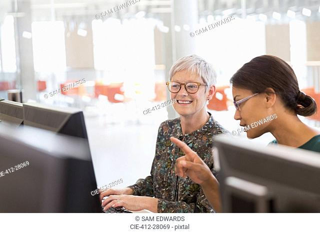 Women working at computers in adult education classroom