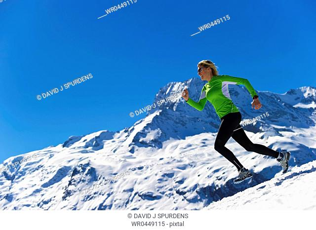 A woman jogging in high snowy alpine mountains