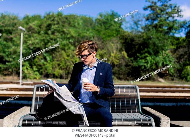 Young businessman with coffee to go sitting on bench at platform reading newspaper