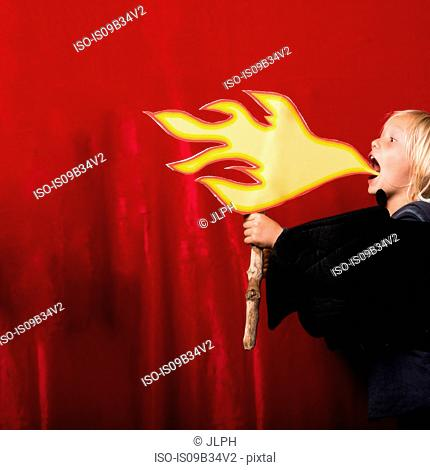 Boy holding cardboard cut-out of flames pretending to breathe fire