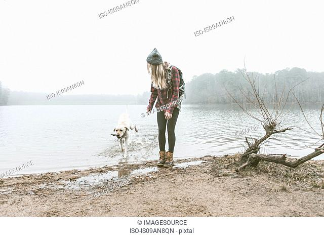 Young woman playing with her dog on misty lakeside