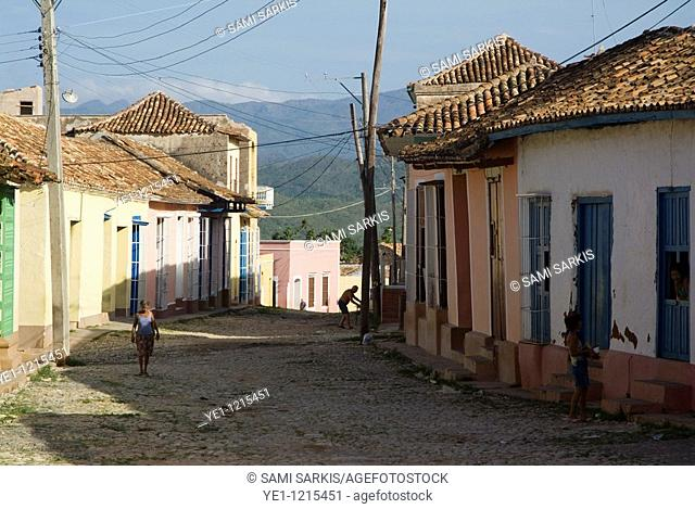 Woman stopping for a chat with her neighbour on a residential street, Trinidad, Cuba