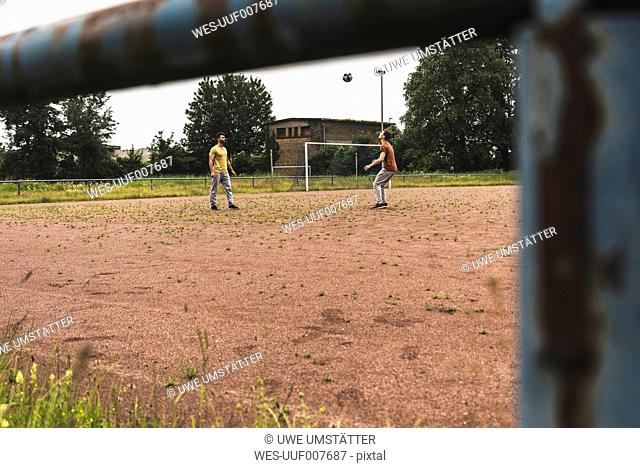 Two men playing football on cinder pitch