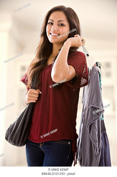 Mixed race woman holding clothing