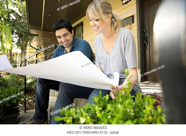 Couple looking at blueprints on front stoop