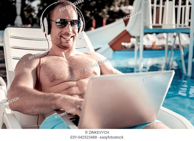 Cannot be better. Excited millennial guy wearing headphones and sunglasses typing something and beaming while sunbathing at a pool