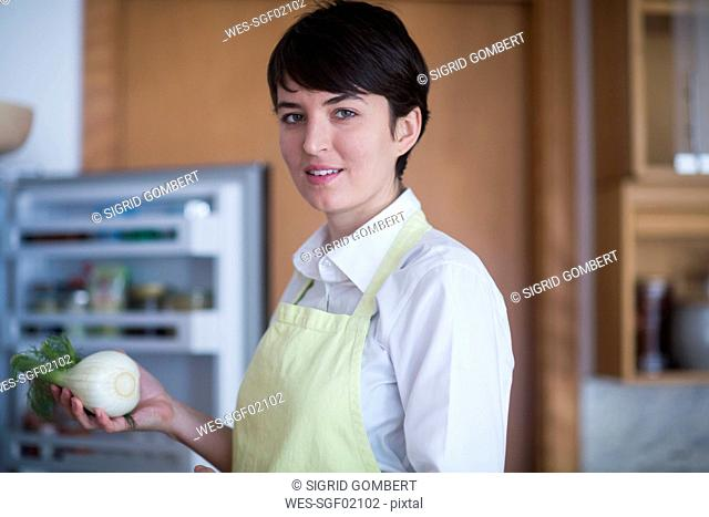 Portrait of young woman with fennel corm in the kitchen