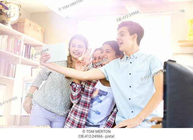 Teenagers taking selfie with digital tablet in room